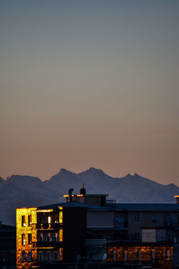 Silhouette buildings by mountains against clear sky at sunset