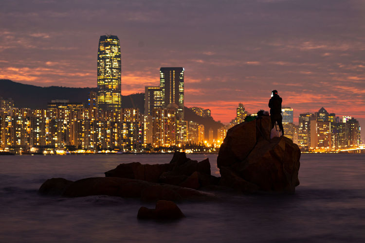 Illuminated cityscape sitting by modern buildings against sky during sunset