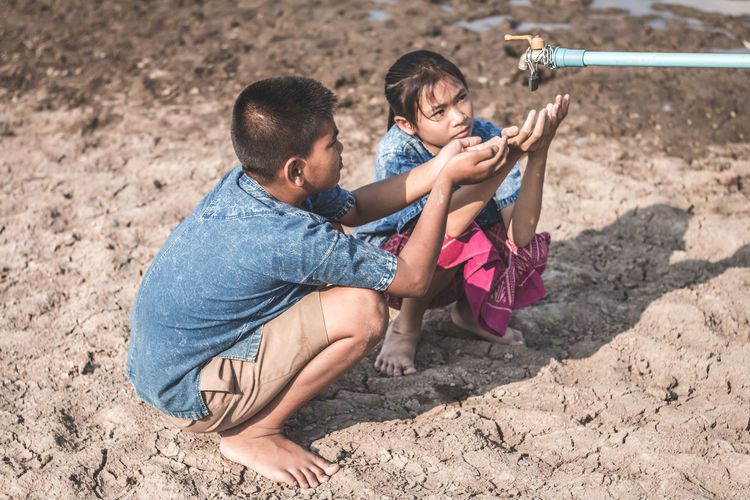 Siblings Crouching By Tap On Drought Field