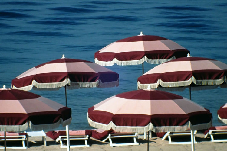 Patterned parasols on shore at beach