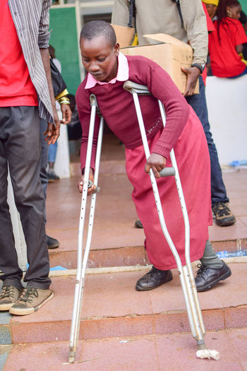 a girl walking on crutches Boys Casual Clothing Childhood Crutches Day Disabled Elementary Age Full Length Incidental People Leisure Activity Lifestyles Low Section Men Outdoors Real People Standing Togetherness Two People