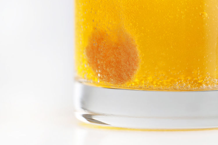 Orange effervescent bubbles of calcium and vitamin C in transparent glass. Studio Shot Food And Drink Indoors  Close-up Glass Refreshment Drink Yellow White Background Drinking Glass Single Object Food Still Life No People Freshness Household Equipment Copy Space Transparent Healthy Eating Crockery Temptation Vitamin C Calcium Effervescent Tablet Supplement