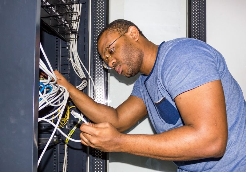 IT Guy working Angola IT IT Support Luanda Room Switch Working Adult Africa Cable Computer Cable Computer Network It Professional IT Support Men Network Server Networking Occupation One Person Racks Repairing Server Room Technician Technology Telecommunication