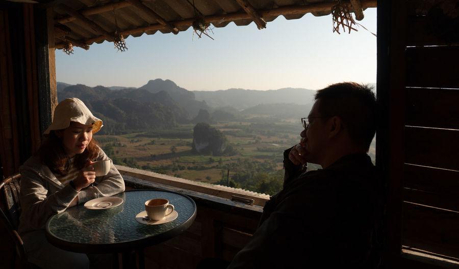 Couple sitting at restaurant against landscape
