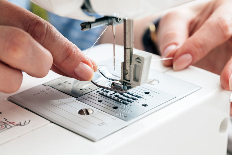Cropped hands of tailor adjusting thread in sewing machine