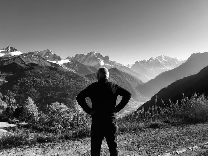 Rear view of man looking at snowcapped mountains against clear sky