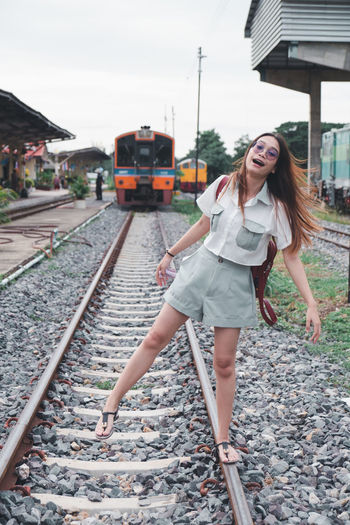 Full length of young woman at railroad station