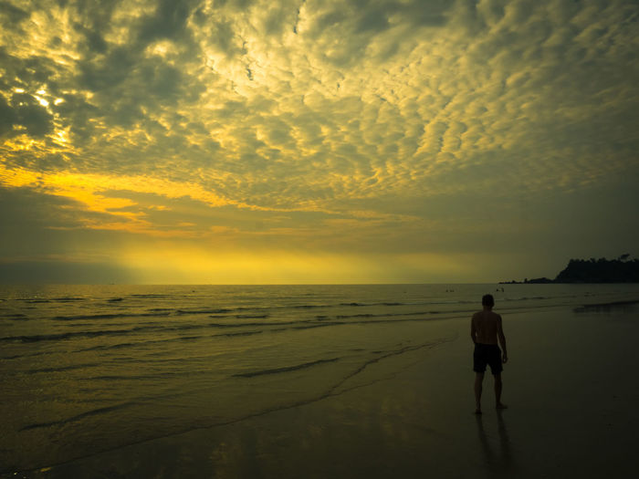 Rear view of man walking at beach against cloudy sky during sunset