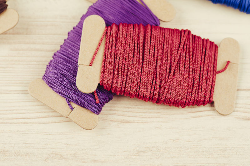 colorful stacking cotton yarn wool on wooden background Still Life Indoors  Textile Table Wood - Material Close-up No People High Angle View Red Art And Craft Clothing Wool Pattern Napkin Hat Pink Color Craft Material Towel Wood Personal Accessory