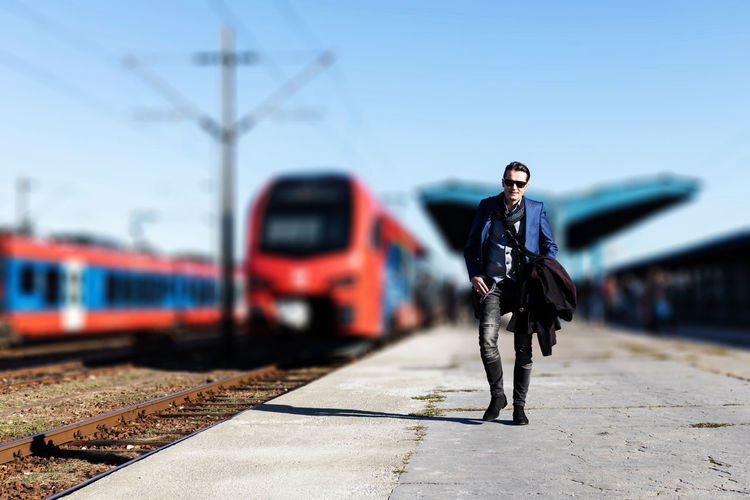 Man standing on train at railroad station platform
