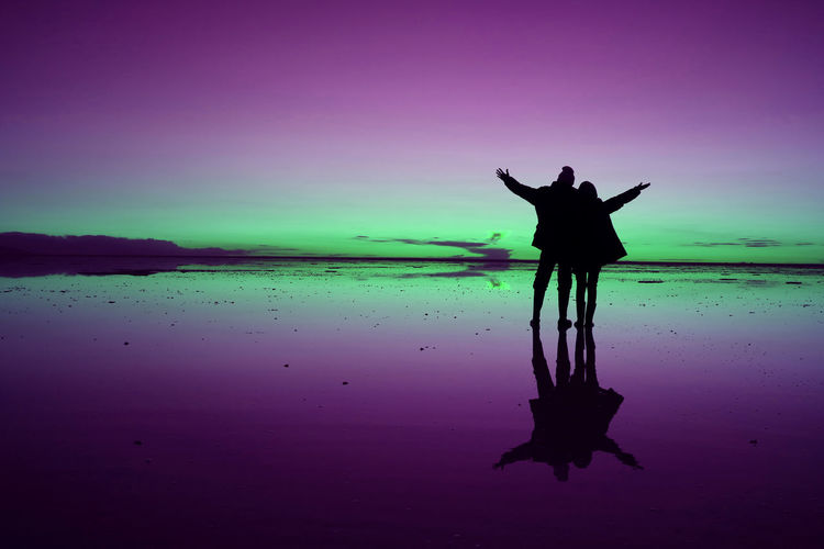 Silhouette couple standing on shore against sea during sunset