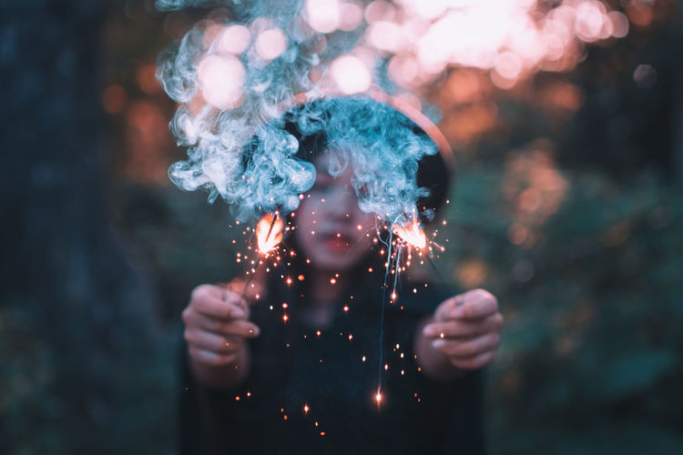 Portrait of a person holding sparkler at night