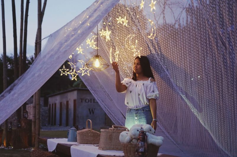 Woman Holding An Illuminated Star While Standing Outdoors