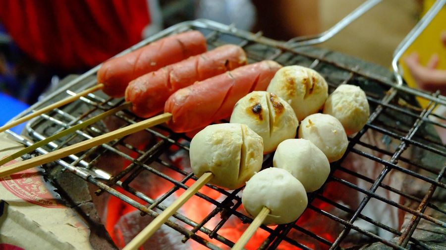 High Angle View Of Fish Balls And Meatballs Cooking On Metal Grate