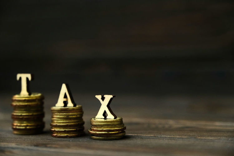 TAX CONCEPTUAL WITH STACKED COIN Arrangement Business Close-up Coin Copy Space Currency Economy Finance Income Tax Return Indoors  Investment Large Group Of Objects Making Money No People Savings Selective Focus Stack Still Life Studio Shot Success Table Wealth Wood - Material