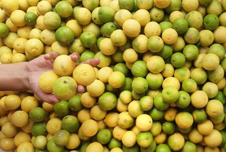 Full frame shot of green and yellow lemon
