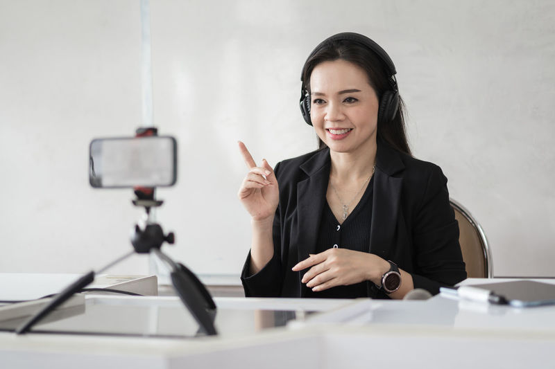 Portrait of a smiling young woman using phone while sitting on table