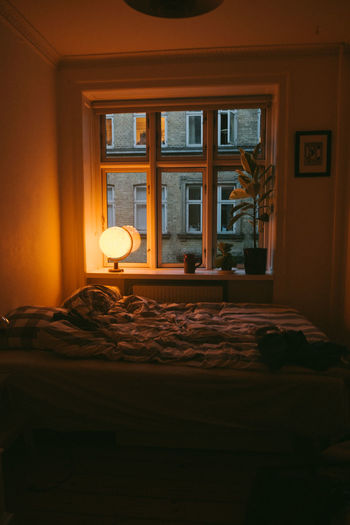 Bed by illuminated lamp on window sill at home