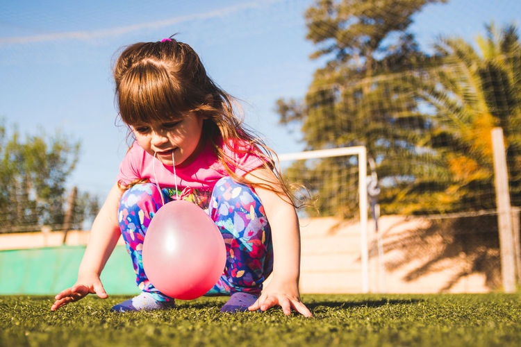 Cute girl with balloon crouching on turf