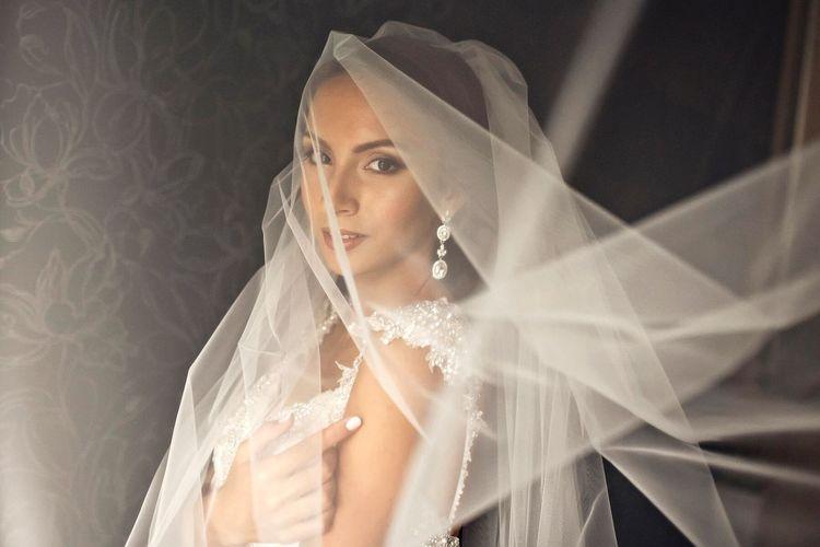 Portrait Of Beautiful Bride Against Wallpaper