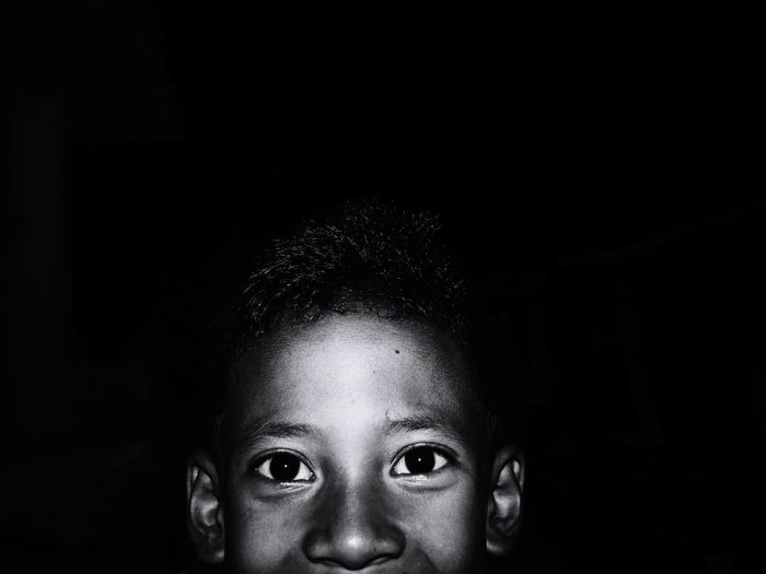 Close-up portrait of boy against black background