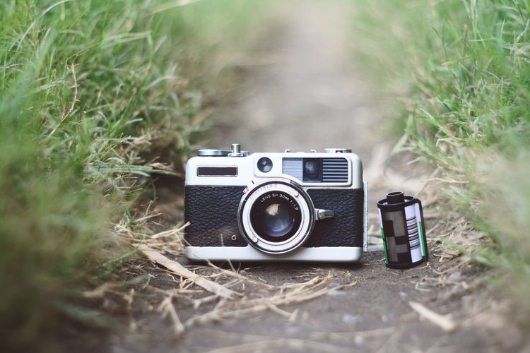 Close-up of old-fashioned camera and reel on dirt amidst grass