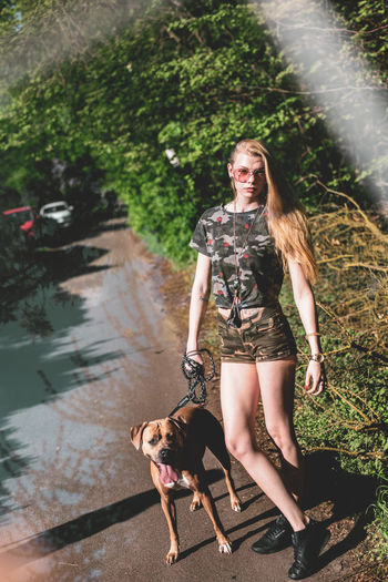 Portrait of young woman standing by dog on footpath