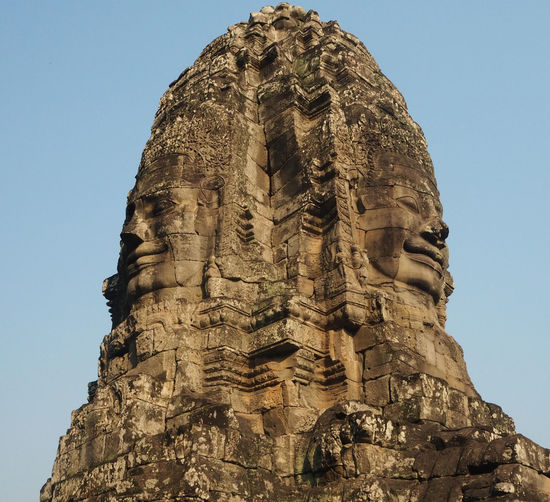Low angle view of sculpture against sky at bayon temple during sunny day