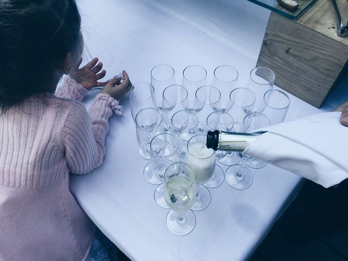 Cropped Image Of Person Pouring Champagne In Flute By Girl