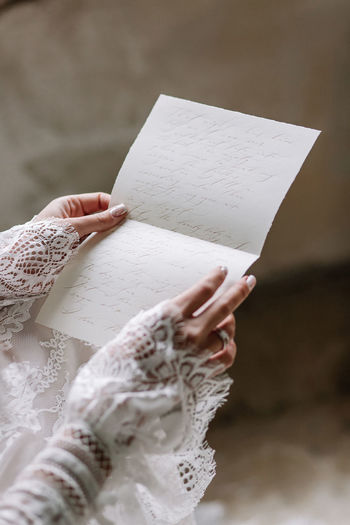 Close-up of woman holding paper with text