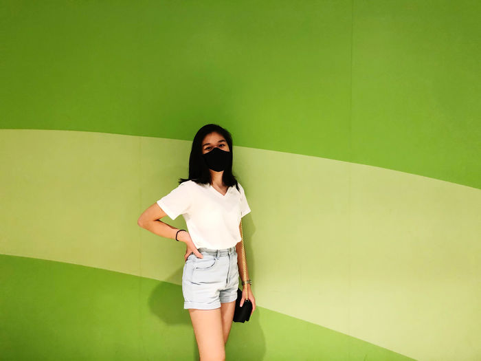Full length of woman standing against wall