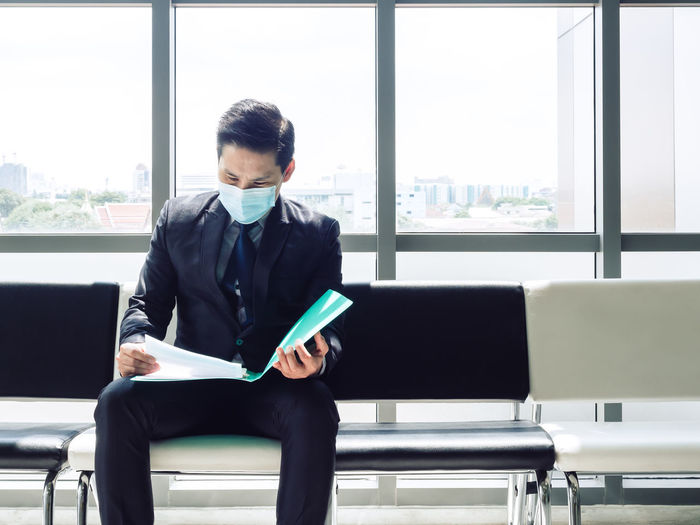 Businessman wearing mask reading documents sitting on seat in office
