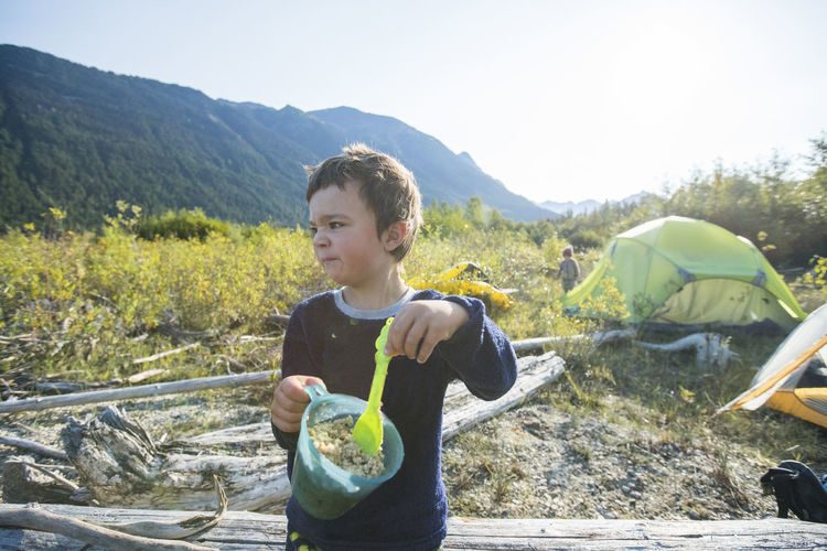Full length of boy holding food on mountain
