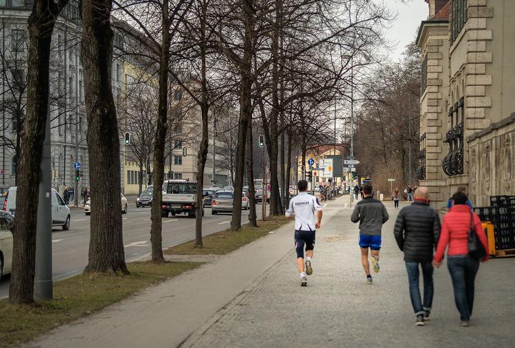Rear view of people walking on footpath in city