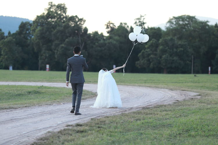 Rear view of couple holding balloons