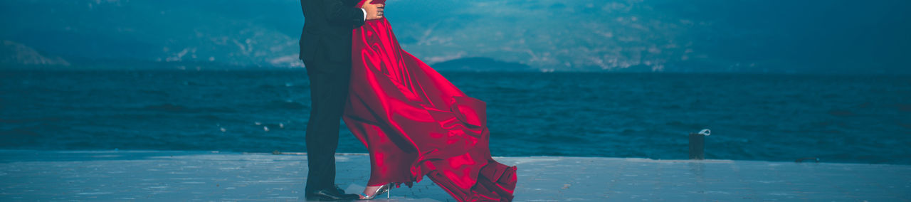 groom and bride in red satin dress Engagement Love Lovers Pier Red Dress Wedding Adult Bride And Groom Clothing Day Glamour Mountain Nature Outdoors Photo Shooting Red Satin Satin Dress Sea Standing Unrecognizable Person Water Wedding Day Wedding Party Women