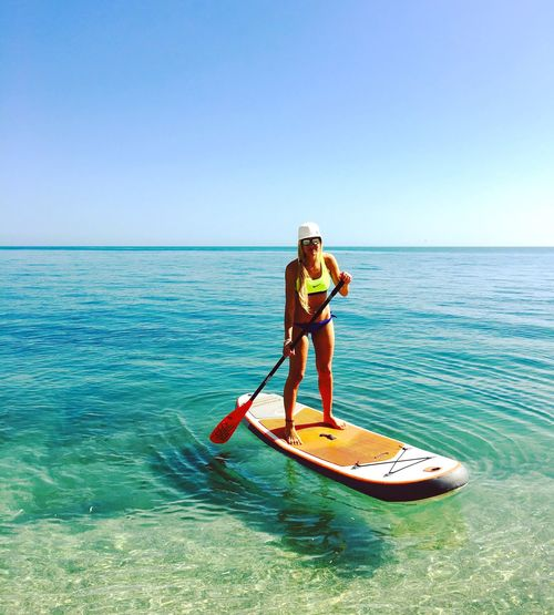 Full Length Sea Vacations One Person Oar Clear Sky Leisure Activity Standing Paddleboarding Real People Lifestyles Water Outdoors Nature Horizon Over Water Adventure Day Blue Weekend Activities Looking At Camera
