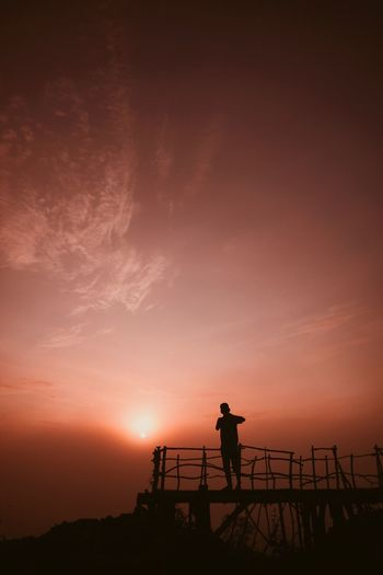 EyeEm Selects Silhouette Sky Sunset Standing Beauty In Nature Lifestyles Tranquility Tranquil Scene Men Water Sea One Person Real People Leisure Activity Orange Color Nature Full Length Scenics - Nature Outdoors