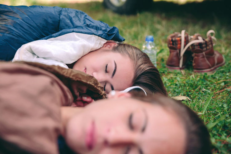 Closeup of young beautiful women friends sleeping in the nature inside of sleeping bags over the grass. Focus on the woman face in the background. Camping Campsite Grass Hiking Horizontal Nature Travel Trip Woman Adventure Backpack Bag Car Caucasian Equipment Female Forest Mountain Off Road Outdoors Sleeping Tent Two People Vehicle Young Adult