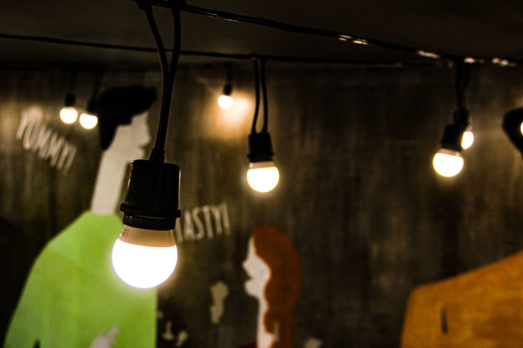 Close-Up Of Illuminated Light Bulbs Hanging By Wall