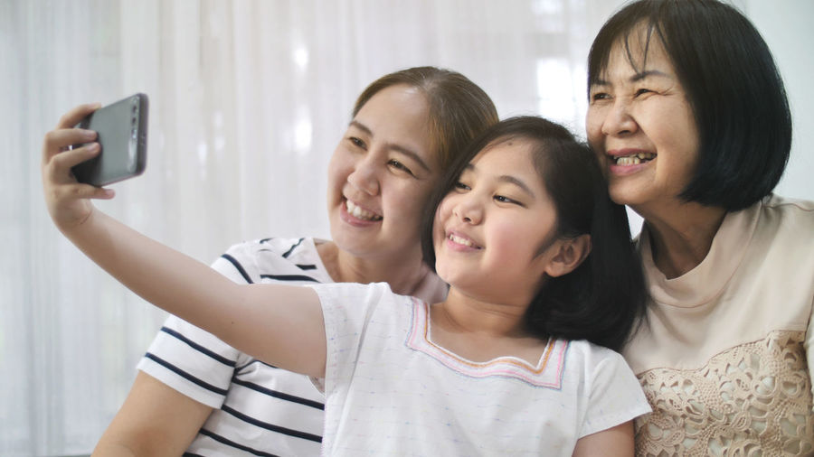 Smiling girl taking selfie with mother and grandmother at home