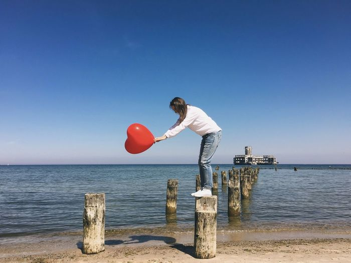 Side view of woman holding heart shape balloon on wooden post in sea against clear sky