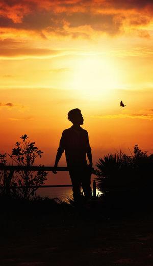 Silhouette man standing by tree against orange sky