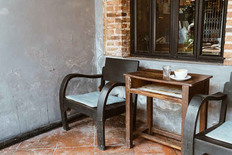 Empty chairs and table against wall in house