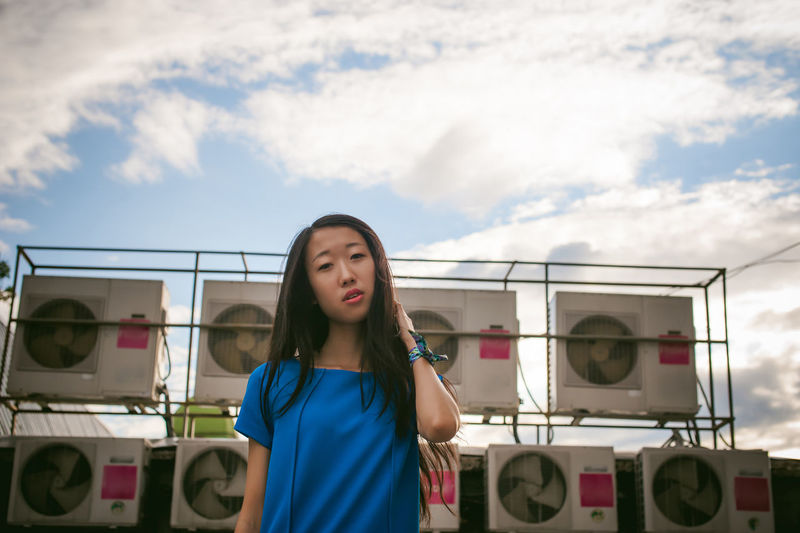 Portrait of young woman standing against exhaust fans