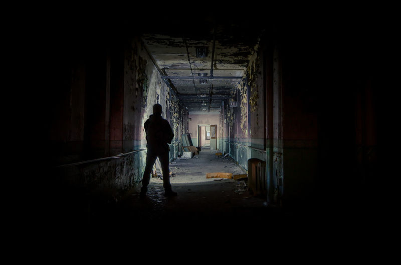 Silhouette man standing in abandoned building