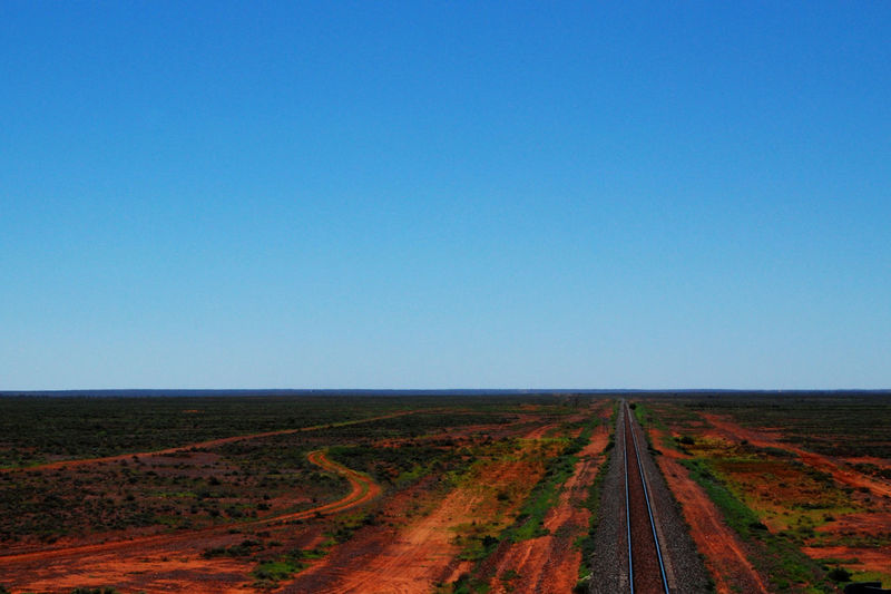 Railway running through the emptiness of outback Australia Australia Beauty In Nature Blue Clear Sky Copy Space Day Desert Emptiness Field Landscape Landscape_Collection Loneliness Nature No People Outback Outdoors Rail Rail Transportation Road Scenics South Australia The Way Forward Tranquil Scene Tranquility Transportation