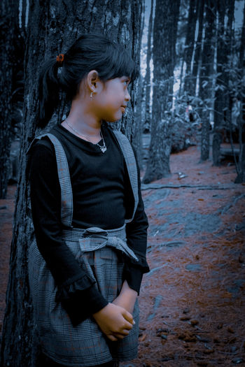 Side view of boy looking away while standing on tree trunk