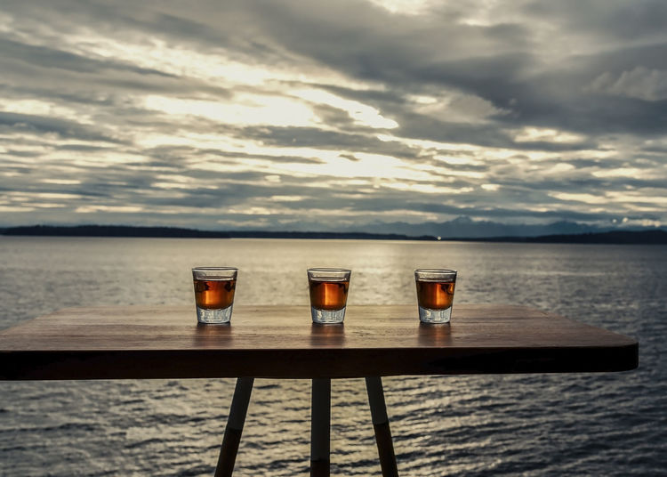 Shots of whiskey on seaside table under dramatic sky.