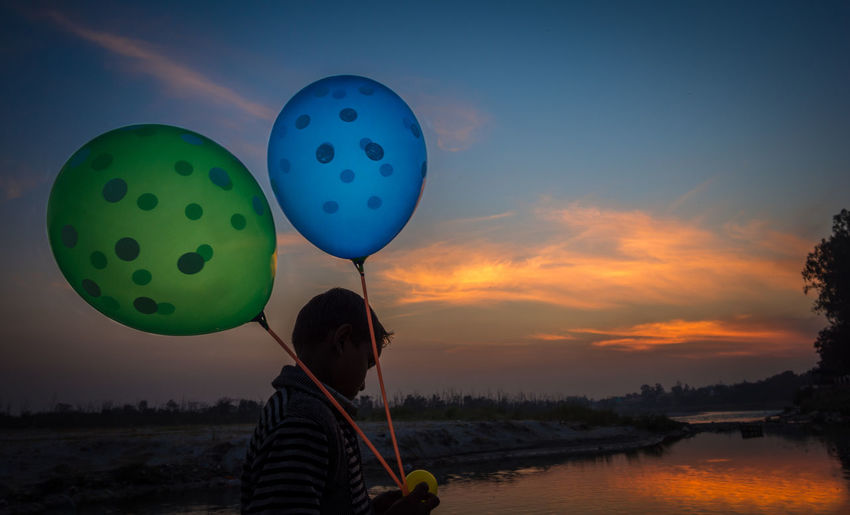 Rear view of man holding balloons against sky during sunset